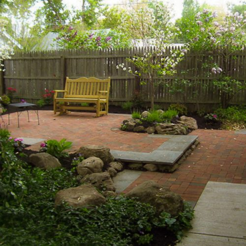 Using boulders in a backyard landscape Renovation project in Rochester NY