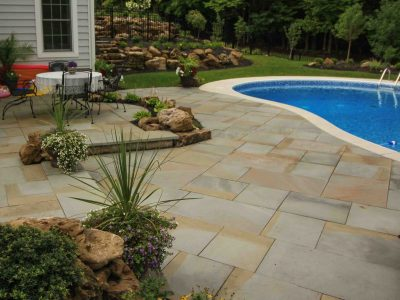 Boulders used for inground pool installation on a sloped yard in Rochester NY