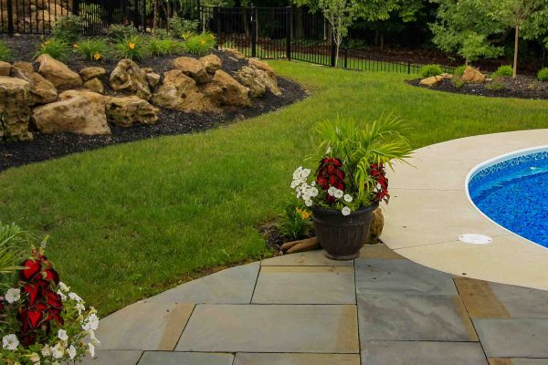 using boulders for a Pool installation on a sloped yard in Rochester, NY